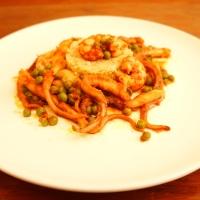 Polipetti in umido con piselli e gamberi serviti con couscous